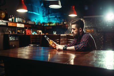 Man sitting at the bar counter, alcohol addiction
