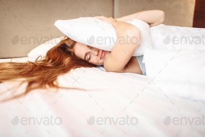 Beautiful woman hugs pillow, waking up