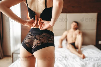 Sexy woman takes off underwear in front of a man