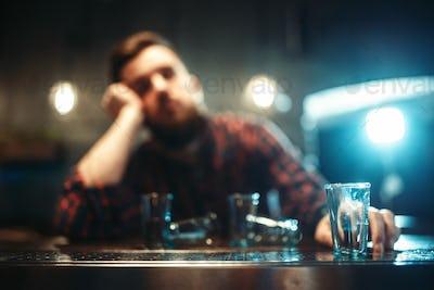 Drunk man sleeps at bar counter, alcohol addiction