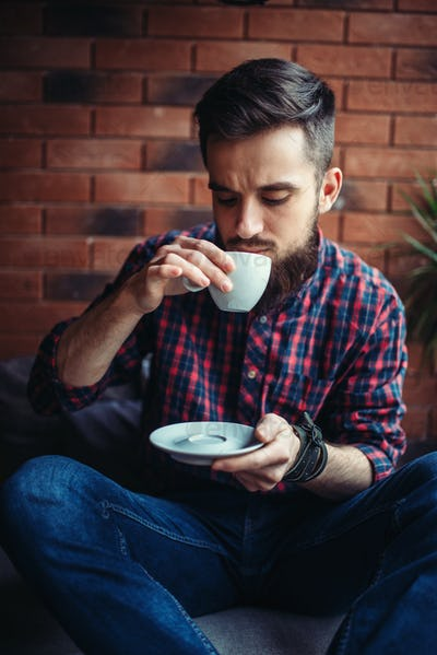 One bearded man drinks coffee in cafe