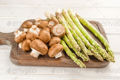 green asparagus and raw brown mushrooms on wooden board