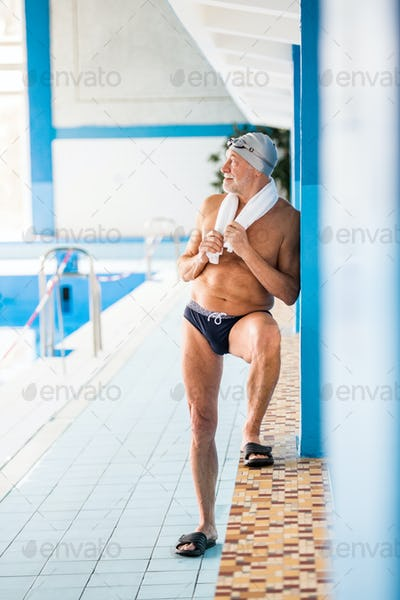 Senior man standing in an indoor swimming pool.