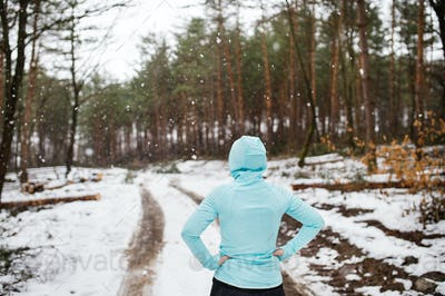Senior woman jogging in winter nature.