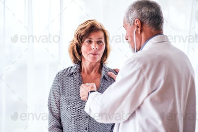 Male doctor examiming a senior woman in his office.