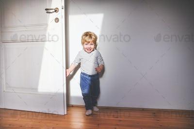Cute toddler boy standing in a bedroom.
