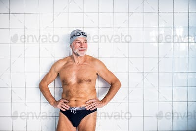 Portrait of a senior man in an indoor swimming pool.
