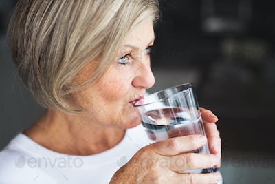 Senior woman drinking water in the kitchen.