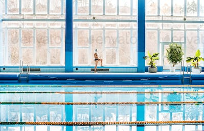 Senior man standing by the indoor swimming pool.