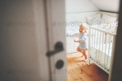 Cute toddler boy running in a bedroom.