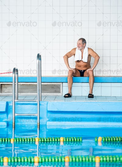 Senior man sitting by the indoor swimming pool.