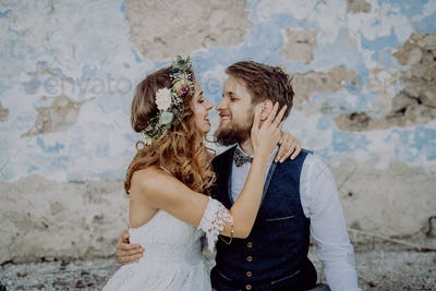 Beautiful bride and groom in front of old shabby house.