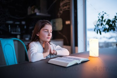 A small girl praying at home.