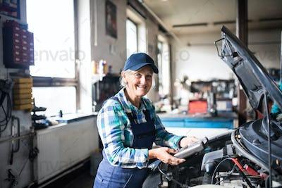 Senior female mechanic repairing a car in a garage.