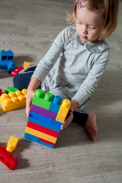 Child girl build of bright plastic construction blocks
