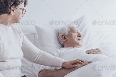 Elderly woman visiting sick husband