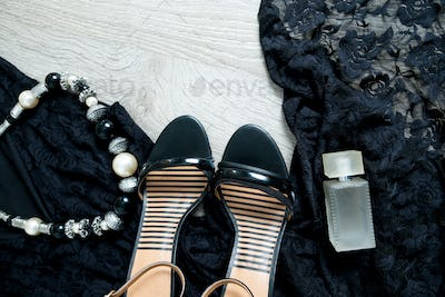 Women outfit. Black lace dress, shoe sandals, necklace and perfume