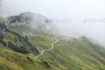 path to wooden cabin in foggy mountains