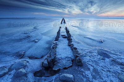 old wooden breakwater in frozen lake