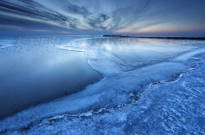 half frozen big lake in dusk