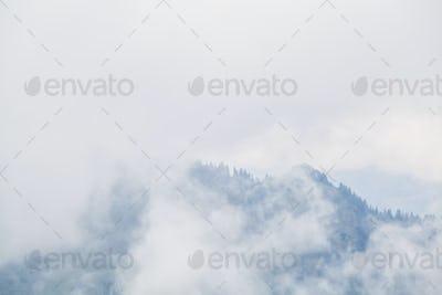 mountain peaks in dense fog