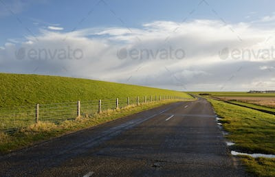 road between green hills and blue sky