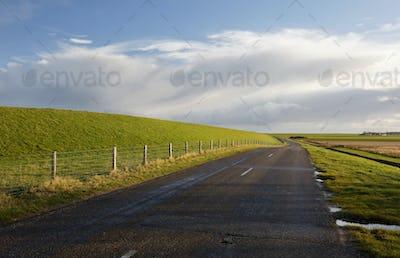 road between green hills and blue sky