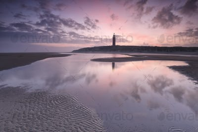 purple sunrise over North sea beach and lighthouse