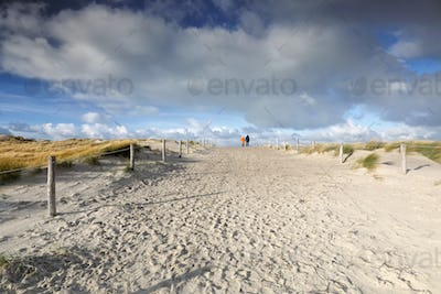 people walk on sand path and blue sky