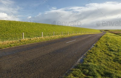 road between green grass hills  under blue sky