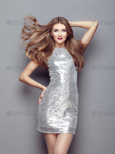 Fashion portrait young woman in elegant silver dress