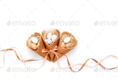 Easter festive background with waffle cones with small eggs on w