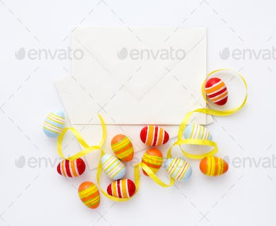 Festive background with easter eggs with ribbons and envelopes.