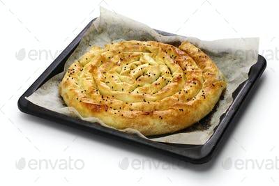 homemade kol borek, turkish savoury rounded pie on oven tray isolated on white background