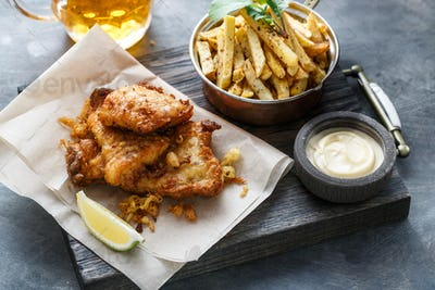 Close view of fish and chips on dark background