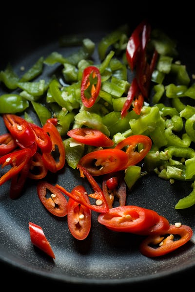 Green and red peppers for fajita in a frying pan closeup