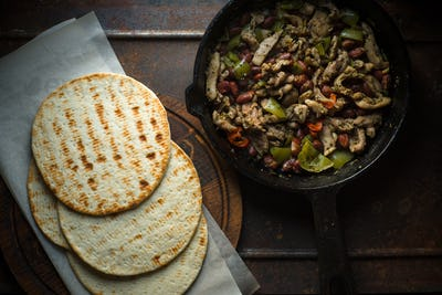 Tortilla on parchment and frying pan with filling