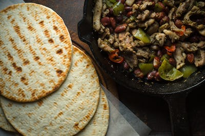 Tortilla on parchment and frying pan with filling closeup