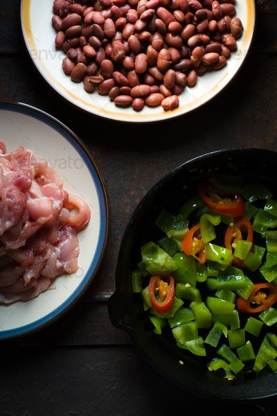 Pieces of chicken, beans. Pepper and chili in a frying pan closeup
