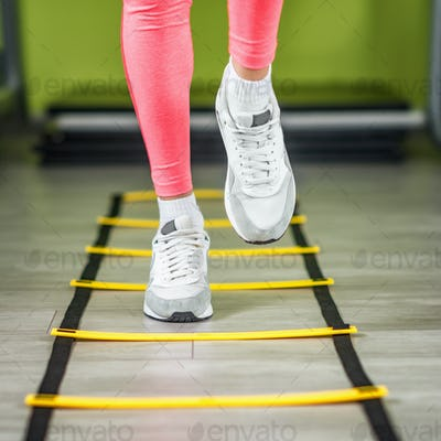 Woman exercising on ladders in the gym