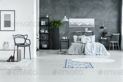 Monochromatic bedroom interior with chair