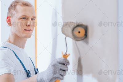 Worker using paint roller