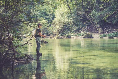 Fly fisherman flyfishing in river