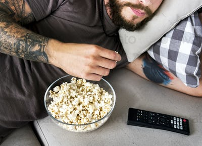 Man lying on a couch watching tv and eating popcorn
