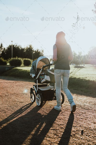 Young mother with a baby carriage walking in a park. Family, child and parenthood concept.