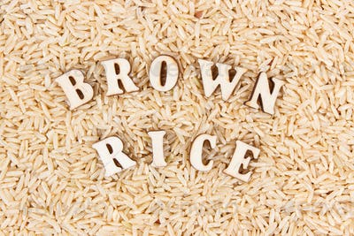 Heap of brown rice with inscription as background, healthy gluten free food concept