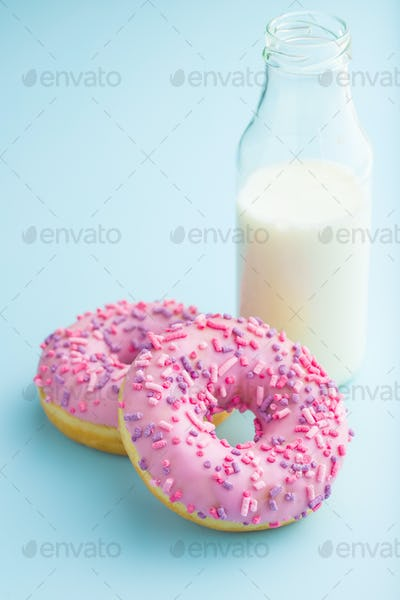 Two pink donuts and milk.