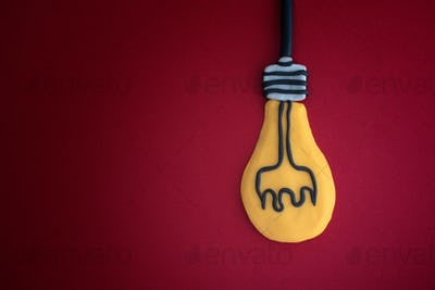 Light bulb made out of play clay on red background