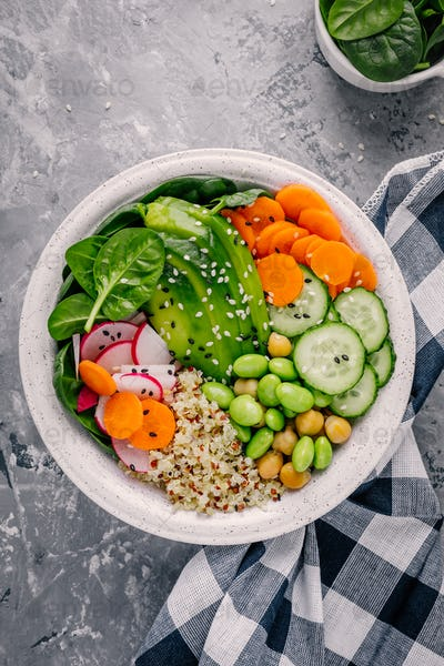Vegan Buddha bowl salad with spinach, quinoa, roasted chickpeas, grilled chicken, avocado