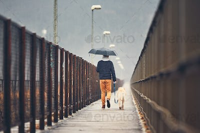 Man with dog is walking in rain